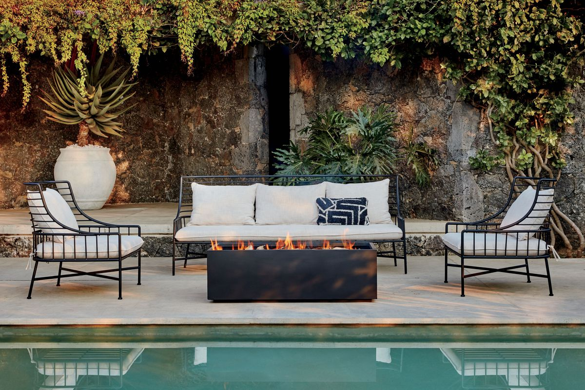A black wire outdoor furniture couch with white pillows sits in front of a fire pit and a pool.