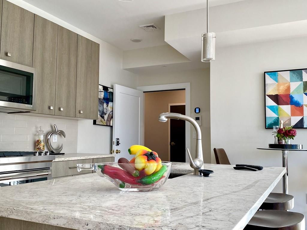 A kitchen countertop with cabinetry visible over it.