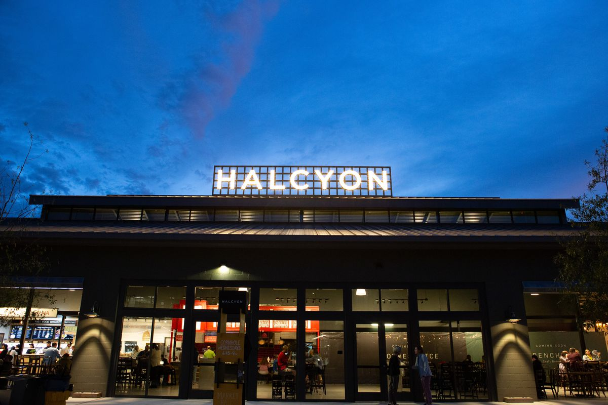 The exterior of Halcyon food hall lit up at night in Alpharetta, Georgia