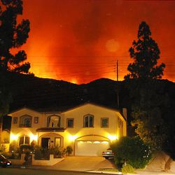Flames from a brush fire glow from a distance behind a home on Baytree Drive in La Canada Flintridge, Calif., Friday.