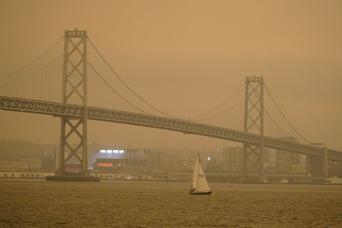 Under darkened skies from wildfire smoke, a sailboat makes its way past the San Francisco-Oakland Bay Bridge and lights at Oracle Park Wednesday, Sept. 9, 2020, in San Francisco.