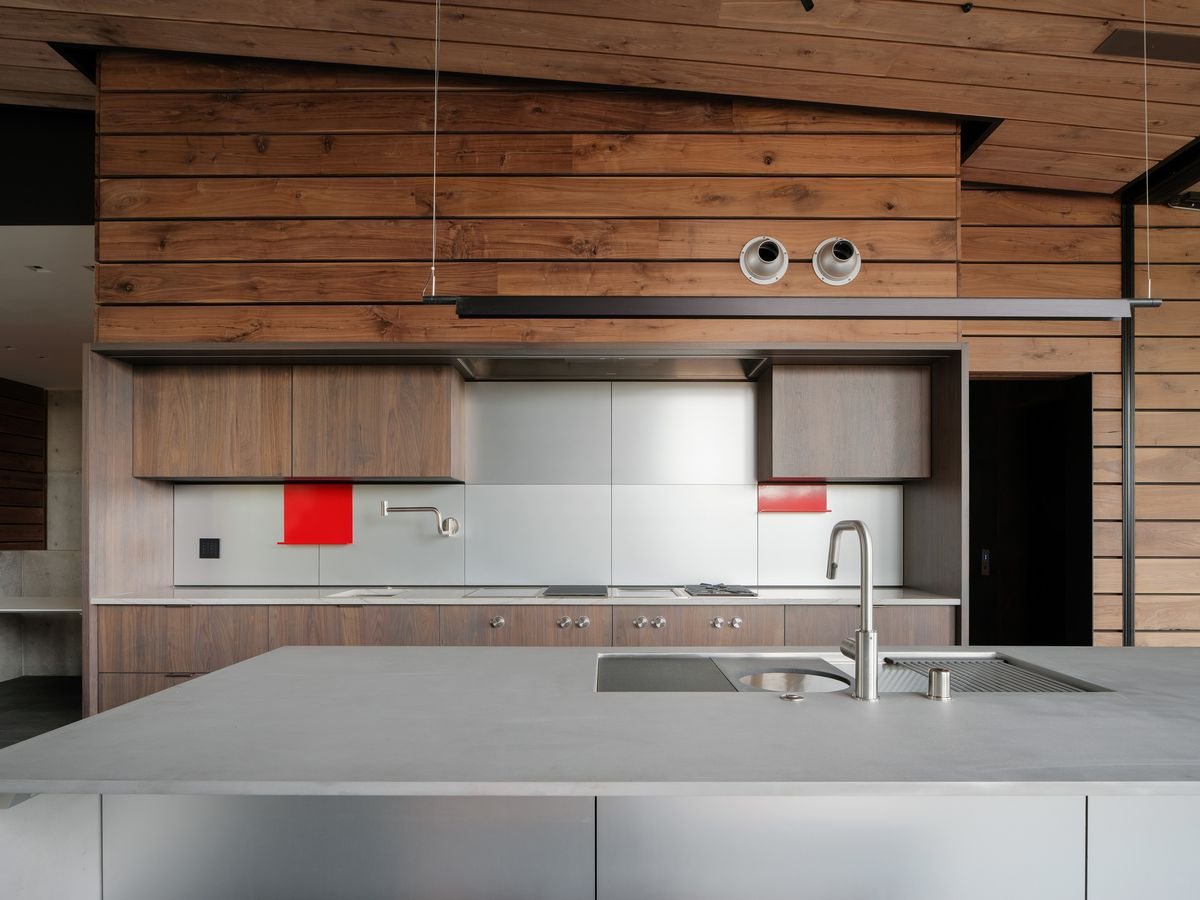 Kitchen featuring wood paneled walls, brown cabinets, and gray island.