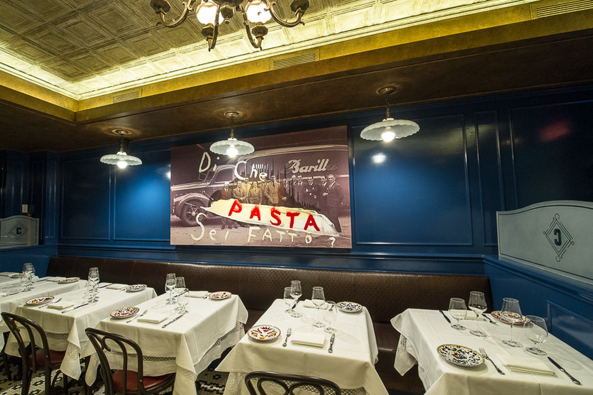 A dining room with blue walls, wall art saying PASTA, and tables with white tablecloths.