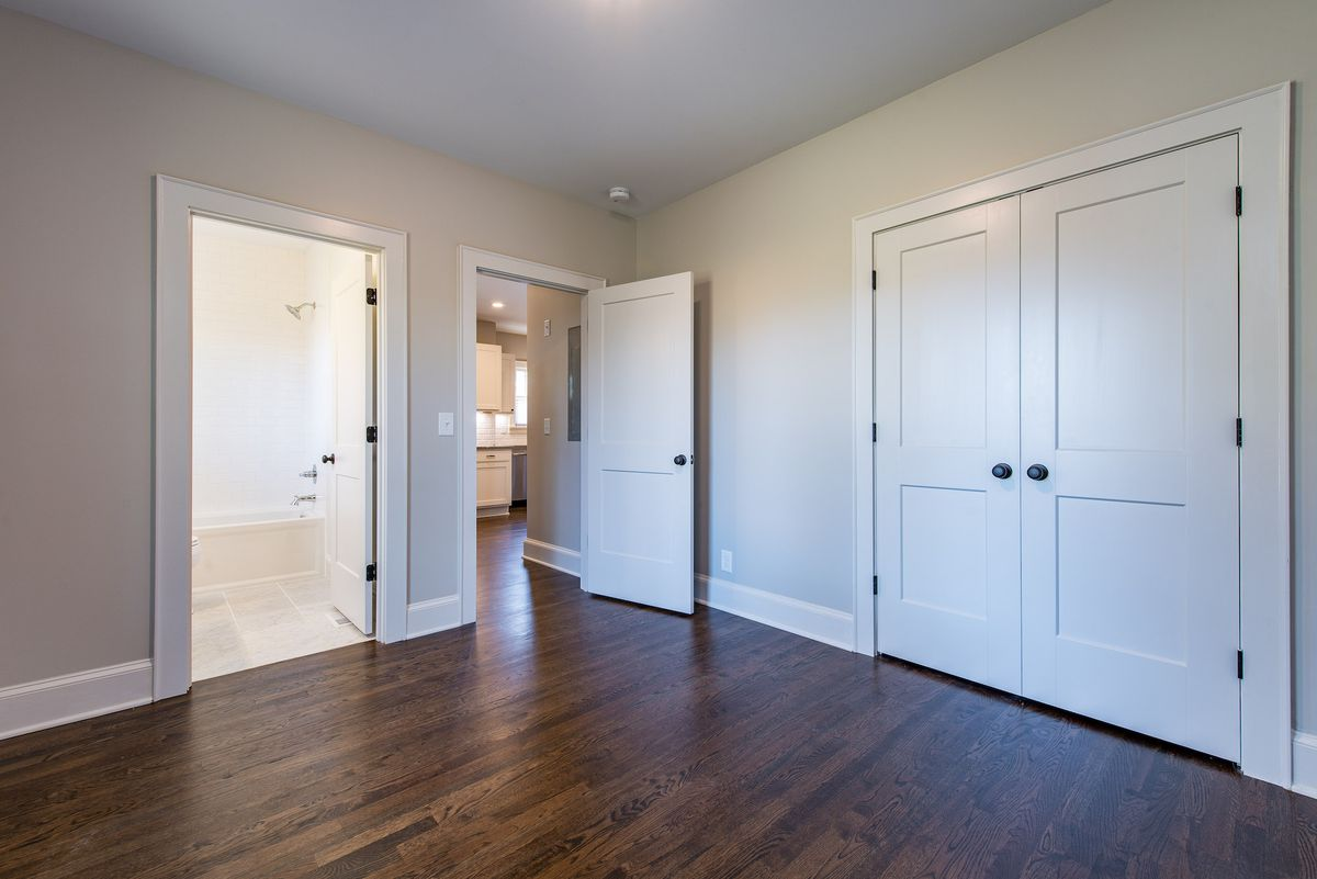 Large empty bedroom with doors leading into a bathroom, out into the kitchen and a double set of closet doors.