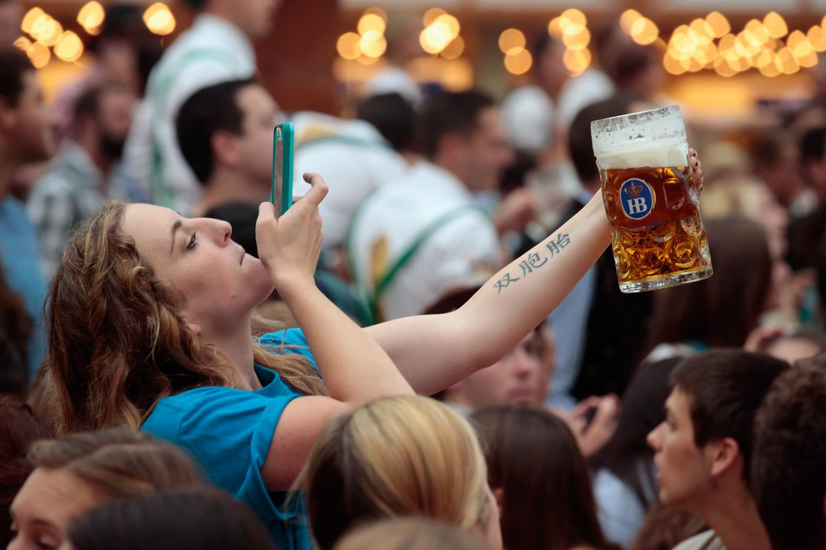 A woman takes a picture of her large mug of beer.