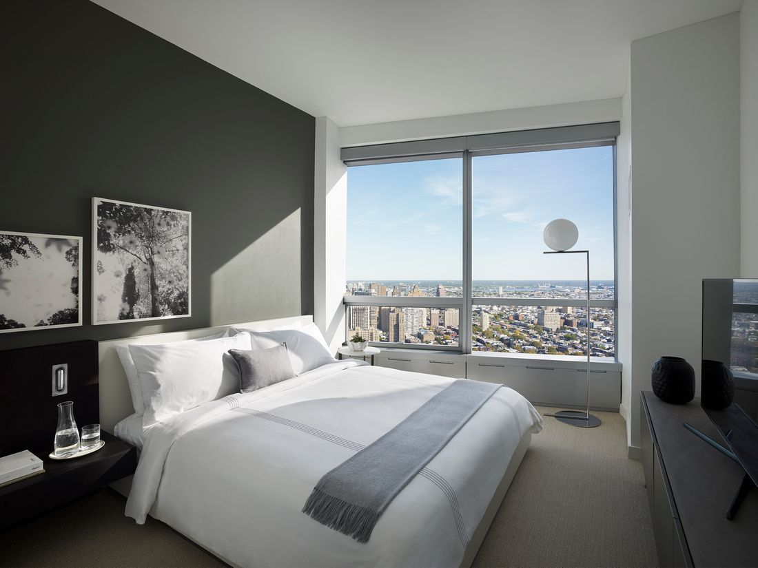 The interior of a room at AKA University City in Philadelphia. There is a large bed with white bed linens, works of art on the walls, and floor to ceiling windows.