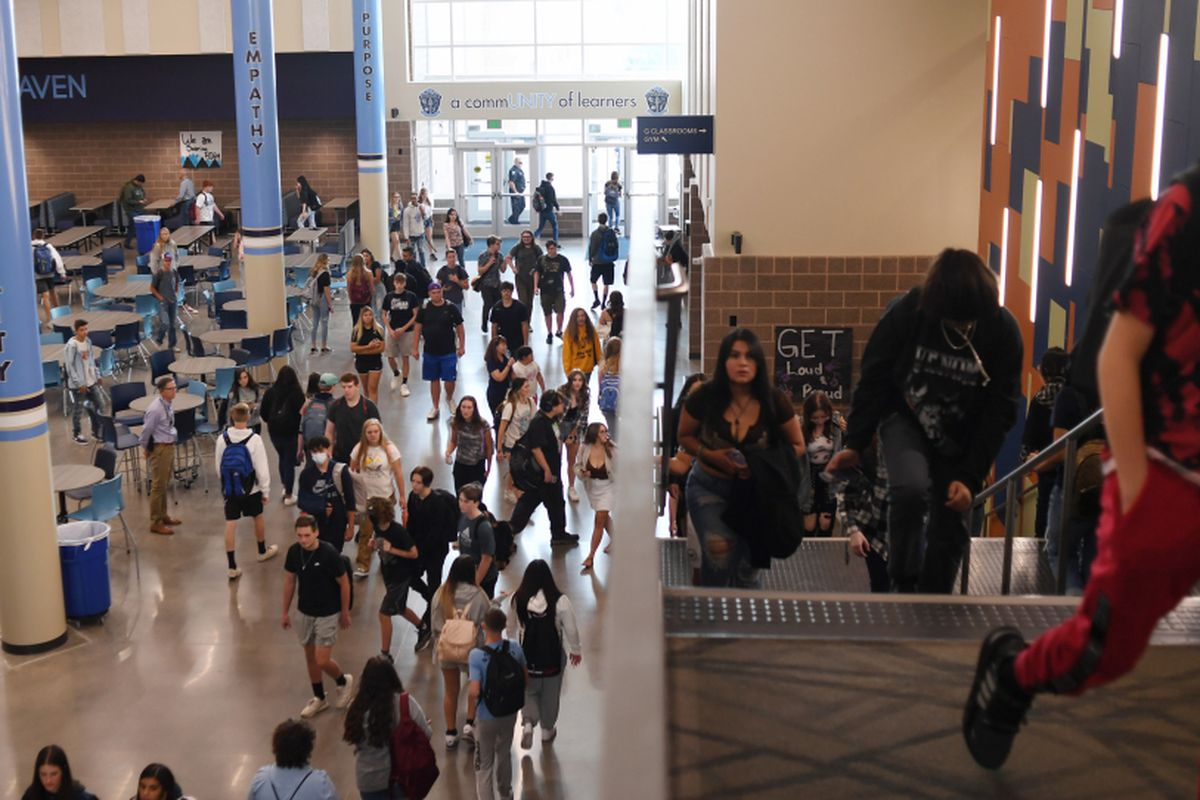 High school students walk up stairs in a hallway during a passing period between classes.