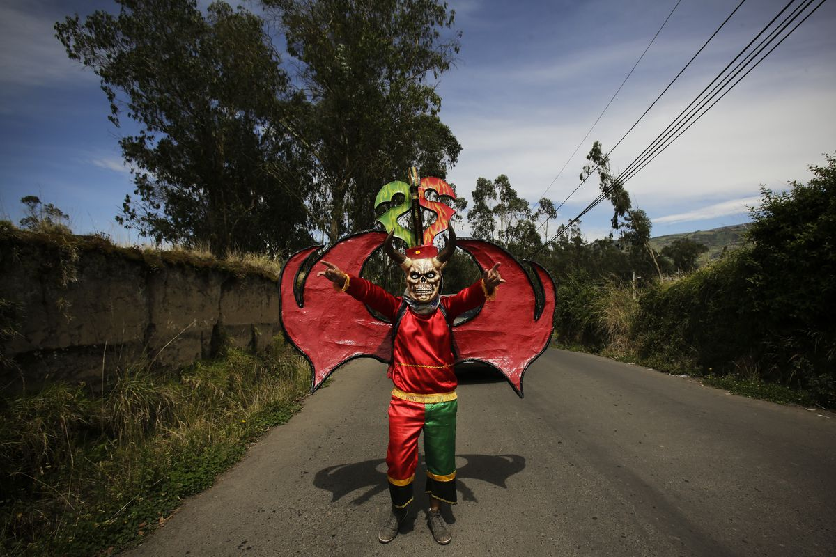 """January 5: Dressed for the traditional New Year's festival known as """"La Diablada"""", a participant strikes a pose in Pillaro, Ecuador. Thousands of singing and dancing devils take over the mountain town for six days of revelry in the streets. Read More. (Do"""