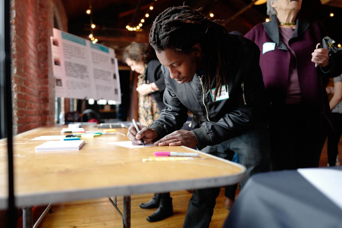 A young man in a black jacket fills out a form providing feedback for a neighborhood design initiative.