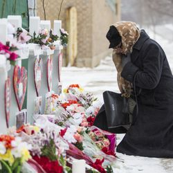 A mourner pays respects Sunday at a memorial for the five people killed two days earlier in a mass shooting at the Henry Pratt Company in Aurora.   Ashlee Rezin/Sun-Times