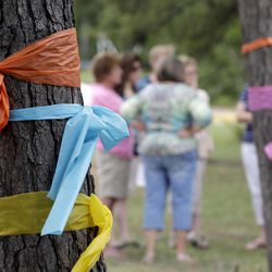 Faculty and parents gather outside Lemm Elementary School after placing ribbons on the trees in honor of those killed in a multiple shooting Thursday, July 10, 2014, in Spring, Texas. Some of the victims were students at the school. The Harris County Sheriff's Office says Ronald Lee Haskell was booked Thursday on a capital murder/multiple murders charge and held without bond. Authorities believe Haskell fatally shot two adults and four children on Wednesday night and critically wounded a 15-year-old girl, who called 911.