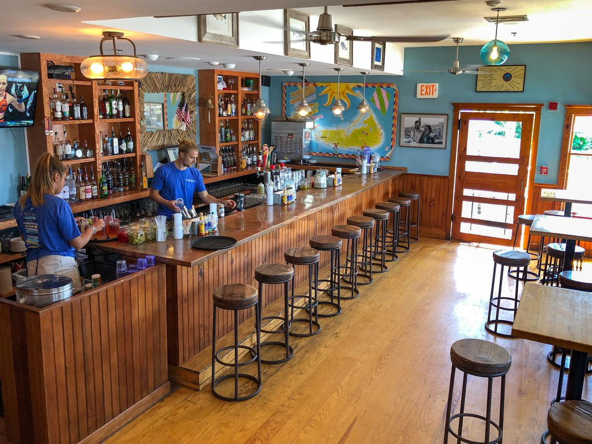 Round wooden stools are lined up along a wooden paneled bar at Millie's, which has bright blue walls, a painting of Nantucket, and beachy vibes