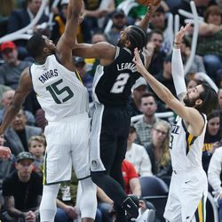 Utah Jazz forward Derrick Favors (15) and Utah Jazz guard Ricky Rubio (3) defend San Antonio Spurs forward Kawhi Leonard (2) in Salt Lake City on Thursday, Dec. 21, 2017.