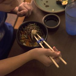 Sam, 11, uses chopsticks to eat the noodle bowl and maki rolls he helped his mother, vegan chef Molly Aubuchon, prepare for dinner Monday, Feb. 8, 2016, in her Kent, Ohio, home.