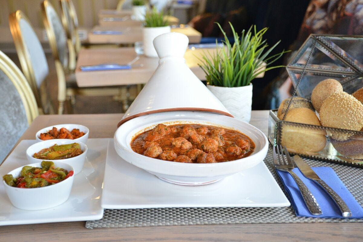 A tagine opened to reveal meatballs inside, alongside a basket of bread and sauces