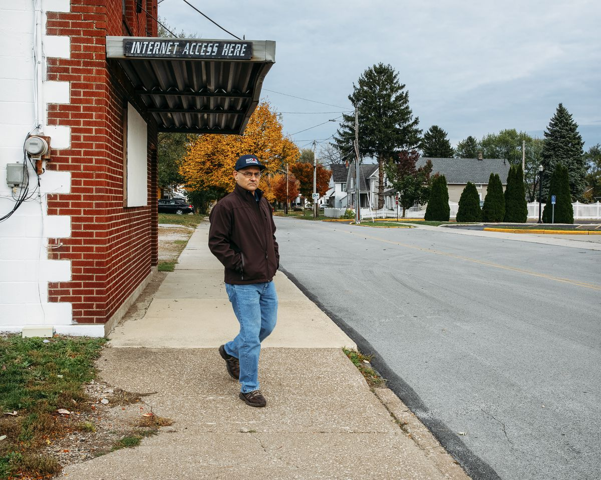 """Noftz, in a brown jacket, jeans, and a blue baseball cap, walks with his hands in his pockets down a cracked sidewalk on an empty street. There are trees with fall colors and homes in the background of the photo; Noftz is passing under a weathered awning; the side reads """"INTERNET ACCESS HERE."""""""