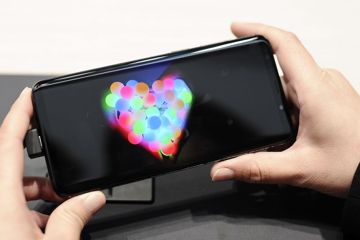 A Samsung Galaxy S9 phone held in two hands in landscape mode, showing a multicolored heart on the screen