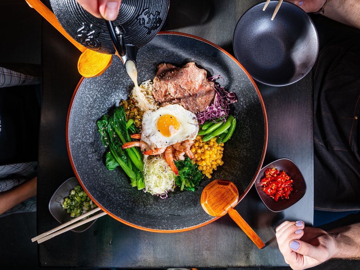 """An 18-inch """"Super Basebowl"""" ($38) for two comes with 8 ounces of ribeye, jumbo shrimp, bean sprouts, corn, seaweed, purple cabbage, sugar snap peas, agaric mushrooms, and a tableside pour of broth."""