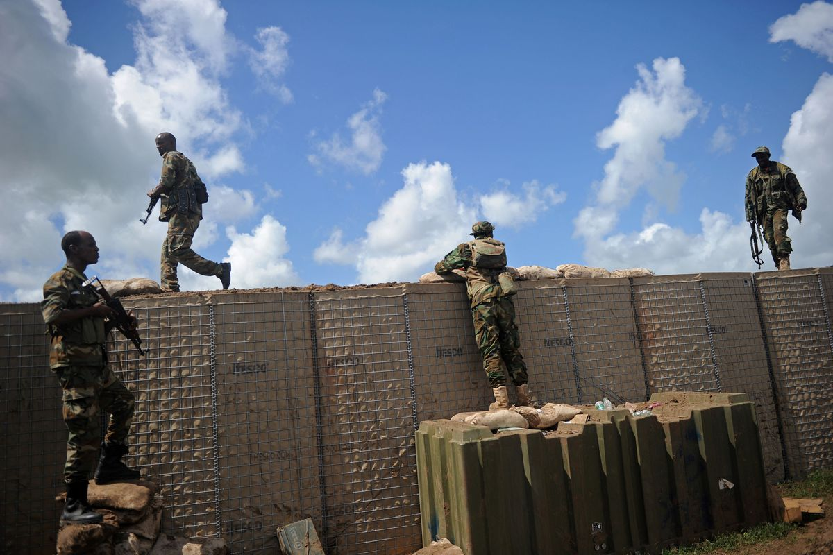 Two men in fatigues stand atop a wall made of brown brick; another stands on a crate and looks over the wall. A fourth stands perpendicular to the wall at attention. All four hold assault rifles.