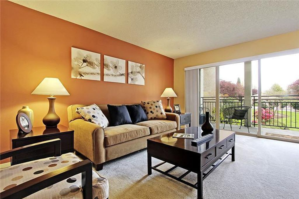 A living room with a balcony through a sliding glass door to the right and an orange accent wall on the left.