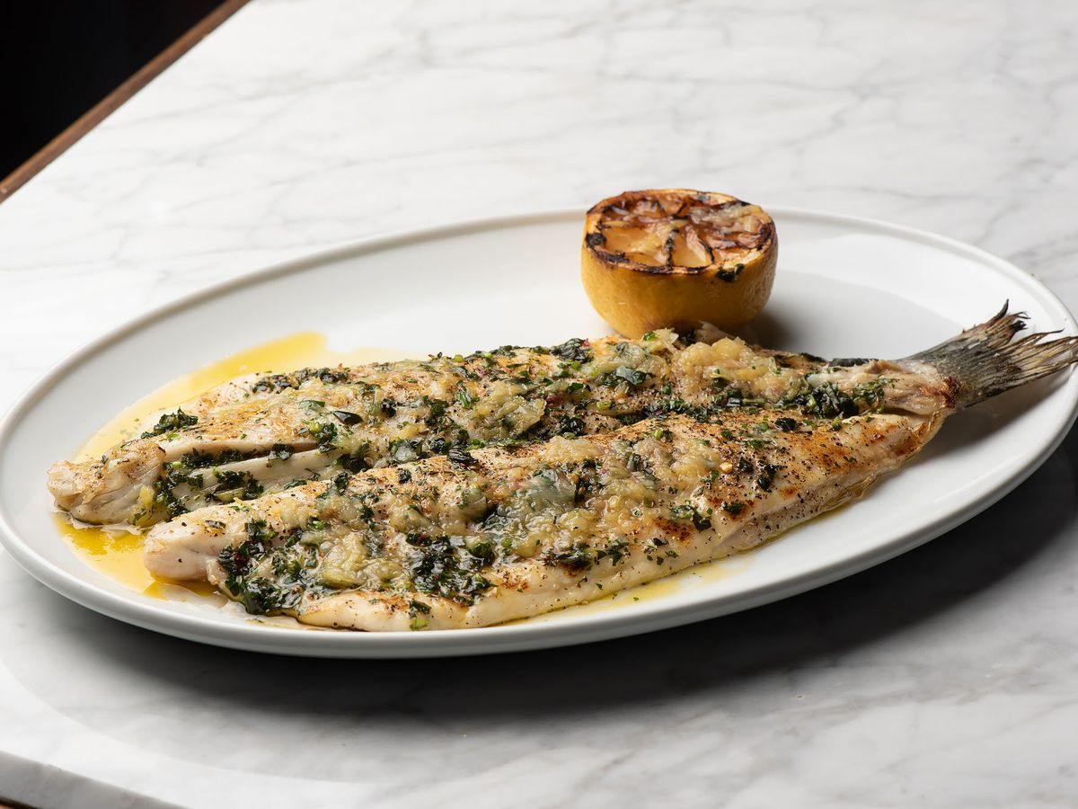 A whole de-skinned fish with grilled lemon on the side.