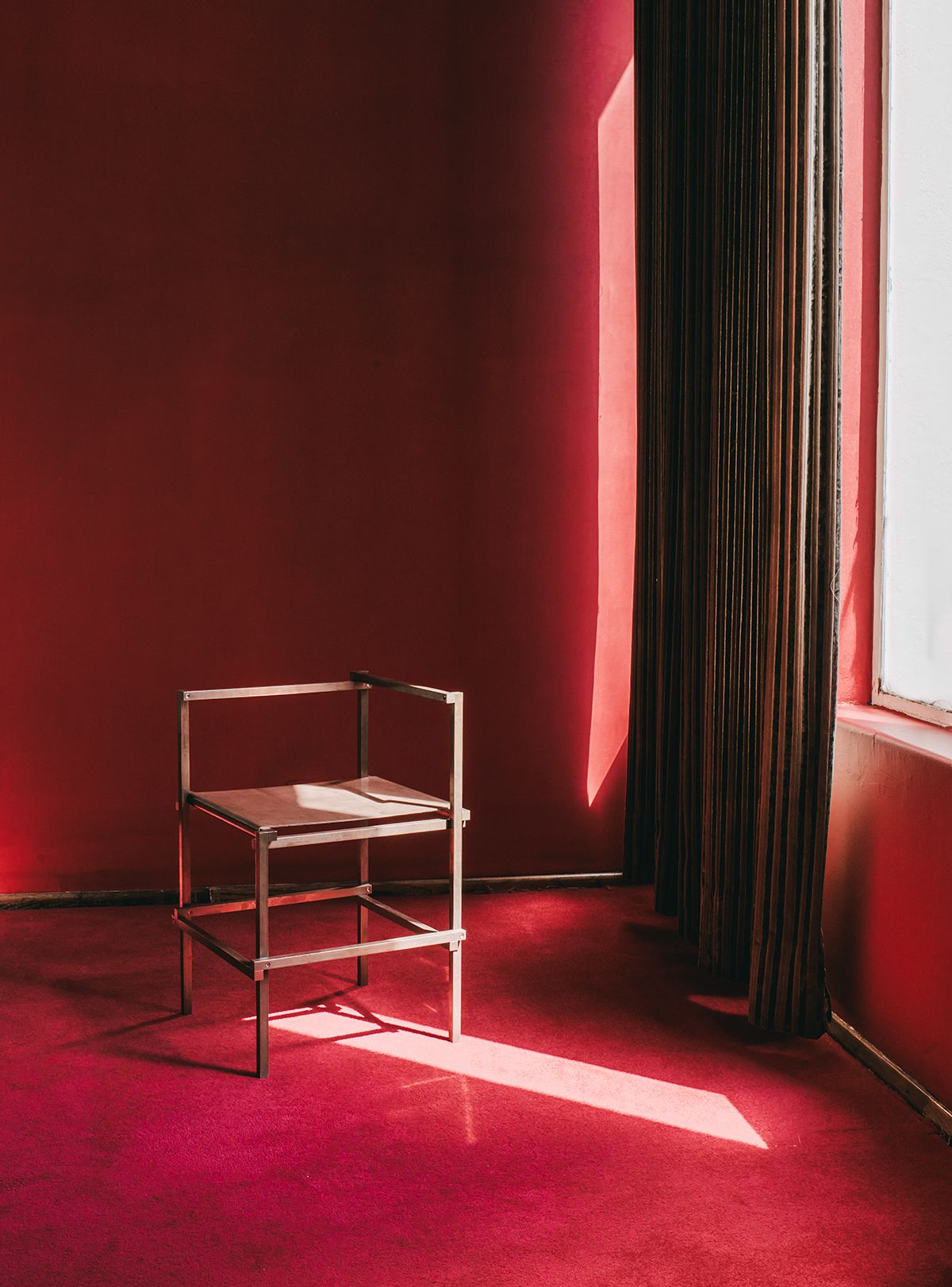 A room with red walls and floors. There is a solitary stool that is sitting in the sunlight streaming in from one window.