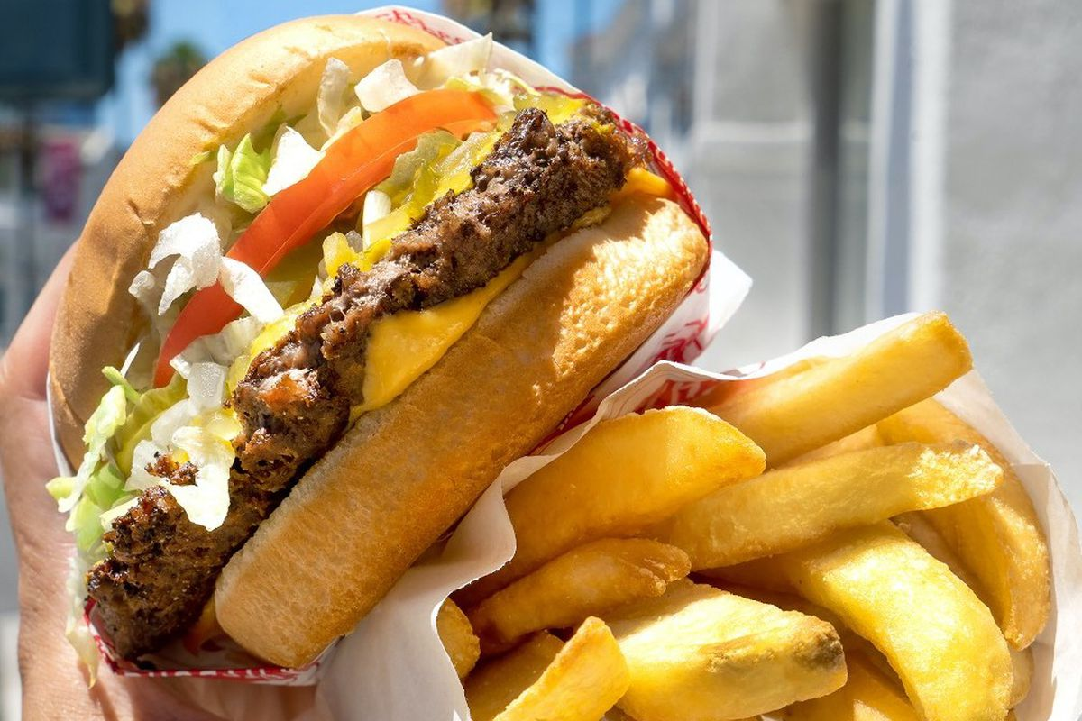 a hand holding both a hamburger and a peper sleeve of thick-cut fries