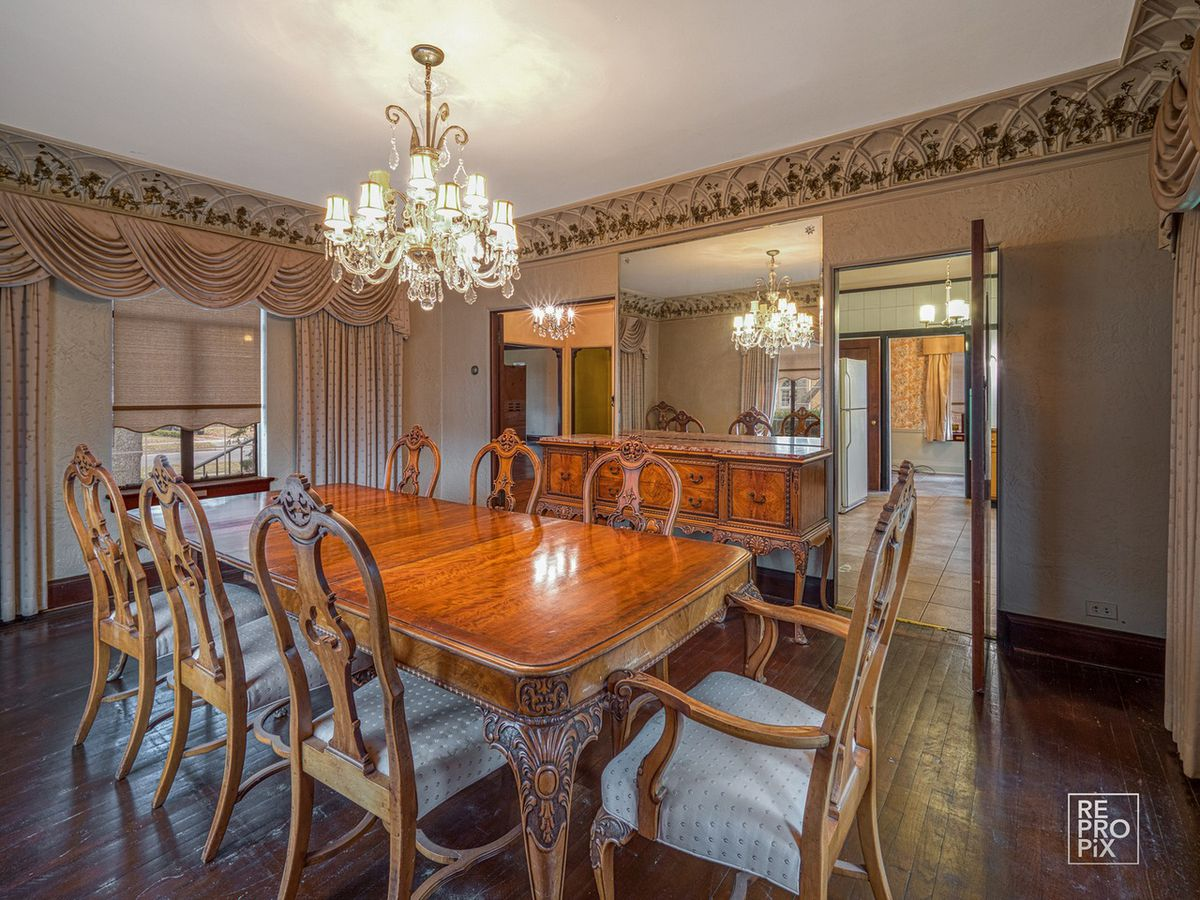 A dining room with elegant curtains, a chandelier, and a large wooden table with seven chairs.
