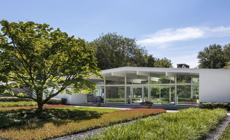 A white house with glass walls sits in front of a garden with red-hued leaves and green bushes.