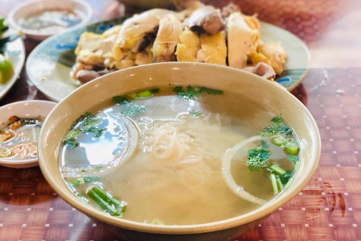 Two bowls of pho broth and noodles with a platter of whole chicken parts