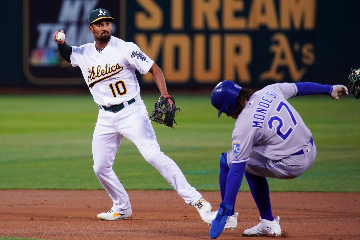 Marcus Semien #10 of the Oakland Athletics turns a double play over Adalberto Mondesi #27 of the Kansas City Royals during the first inning at Ring Central Coliseum on September 17, 2019 in Oakland, California.