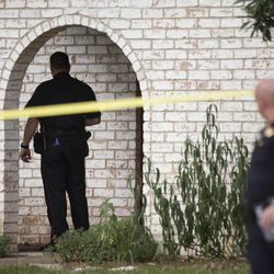 Law enforcement officers investigate the scene of a shooting Wednesday, July 9, 2014, in Spring, Texas. A Harris County Sheriff's Office statement says precinct deputy constables were called to a house about 6 p.m. Wednesday and found two adults and three children dead. Another child later died at a hospital. (AP Photo/Houston Chronicle, Brett Coomer)
