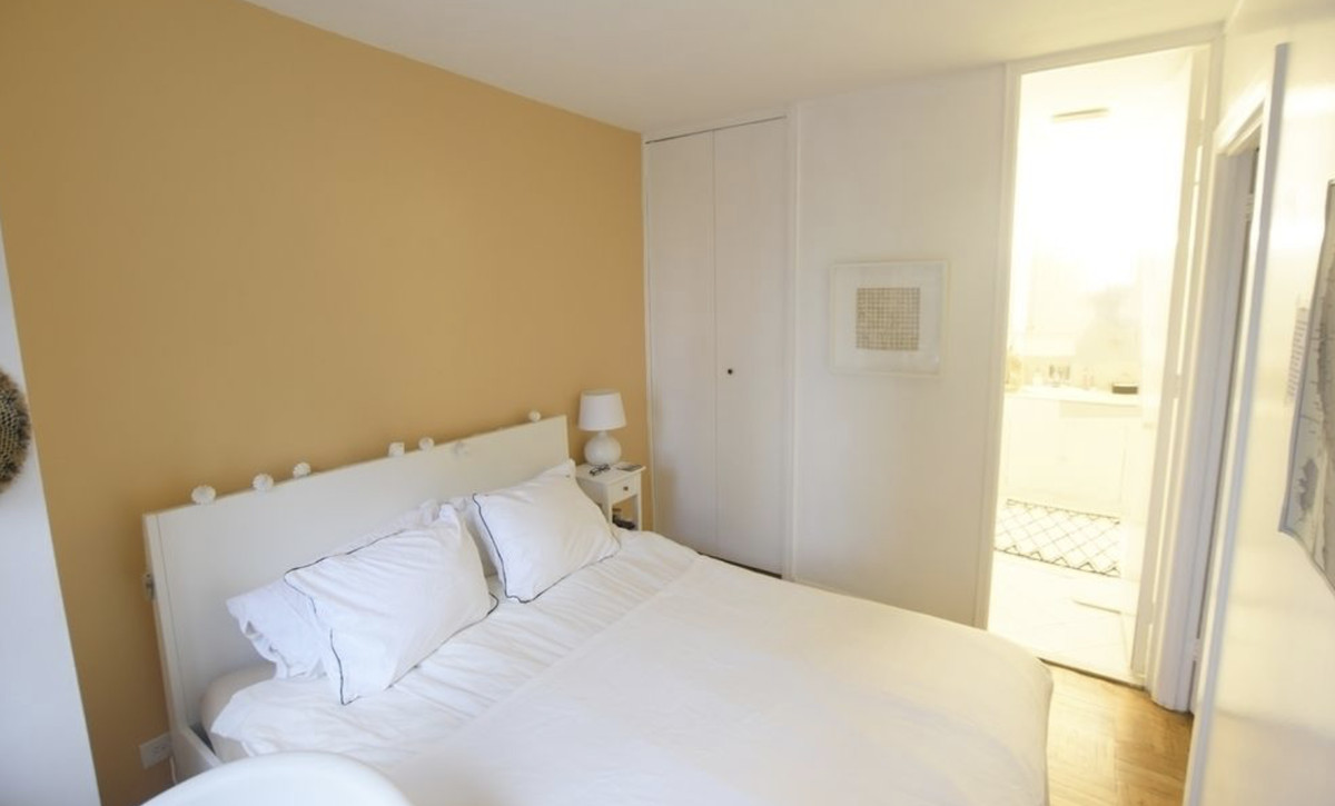 A bedroom with a medium-sized bed, white and yellow walls, and hardwood floors.