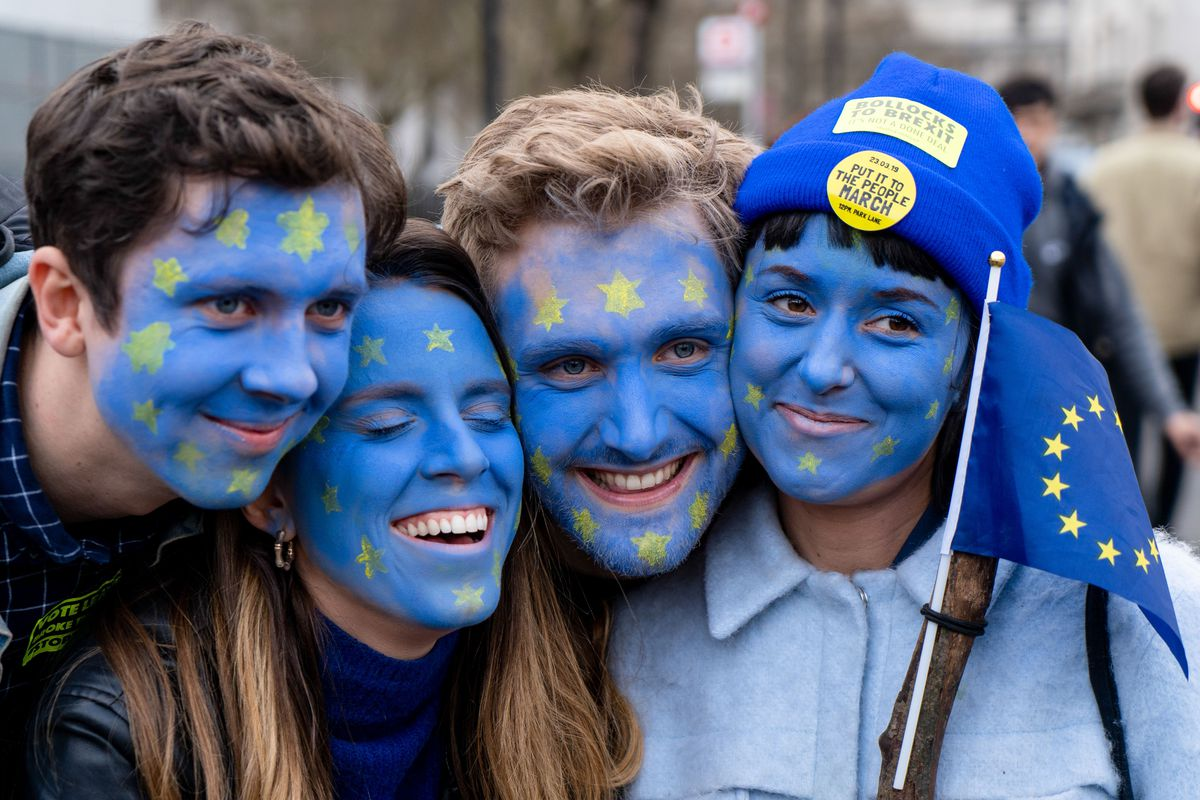 People with their faces painted in EU flag colors participate in the People's Vote anti-Brexit march in London on March 23, 2019.