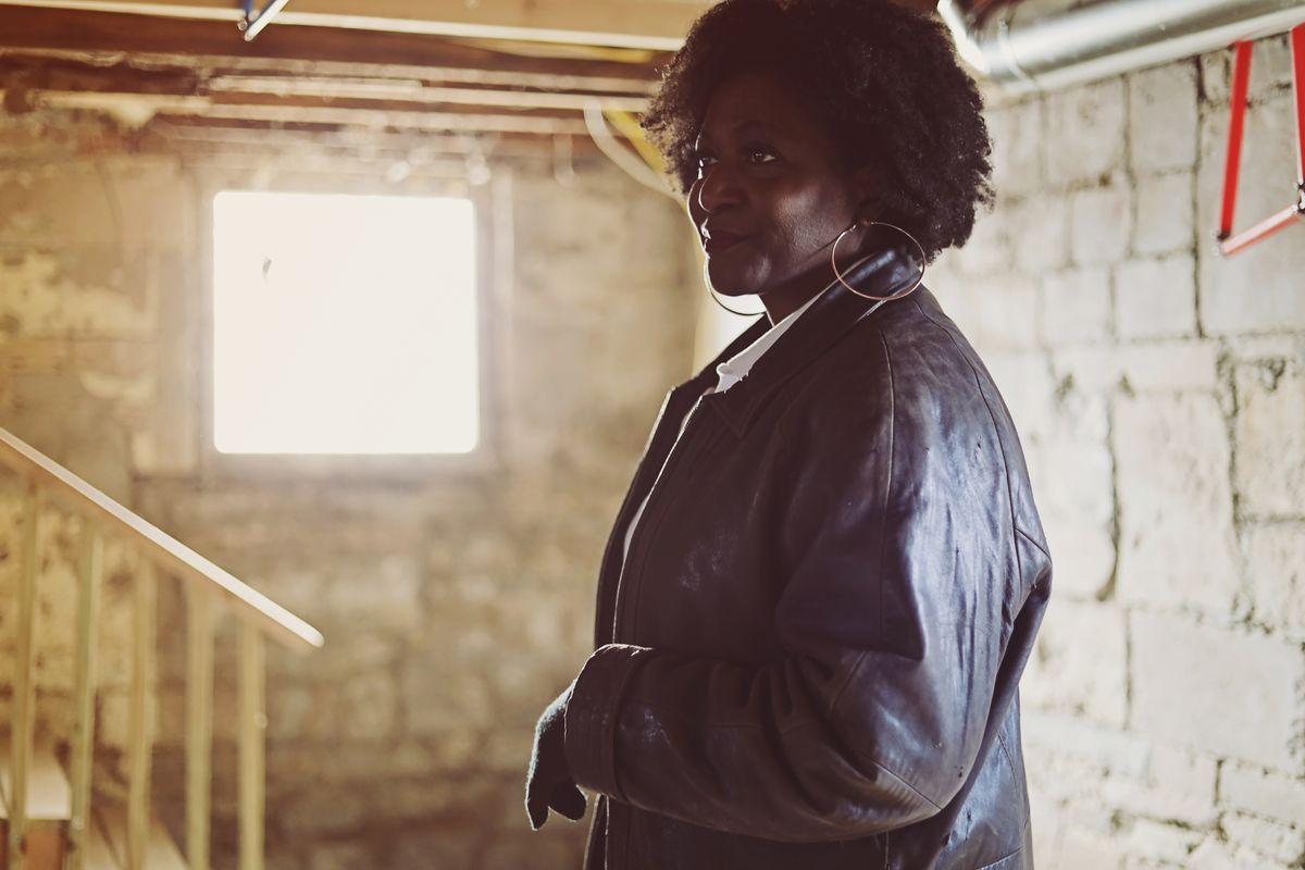 A black woman in a dark coat at a residential work site.