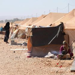 A Syrian refugee woman makes tea in front of her tent at Zaatari Refugee Camp, in Mafraq, Jordan, Sunday, Sept. 2, 2012.