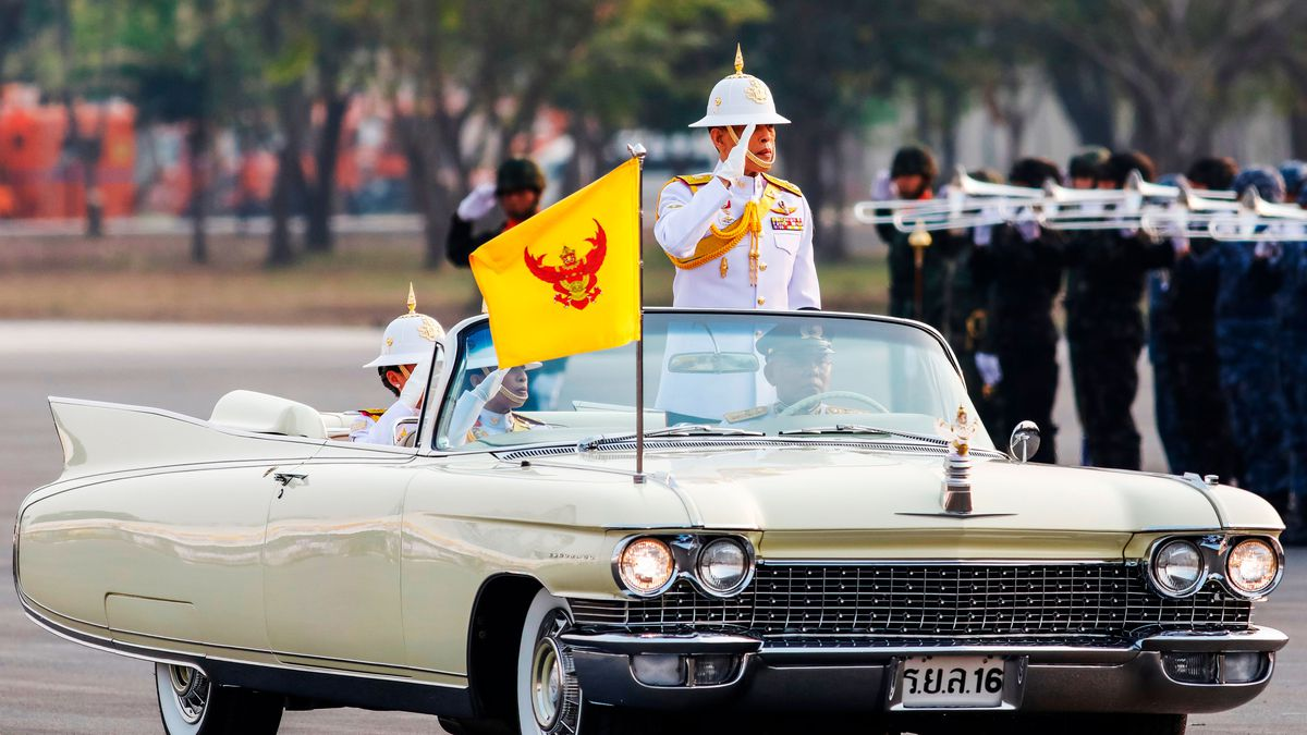 The king of Thailand standing in a 1950s-era convertible and saluting.