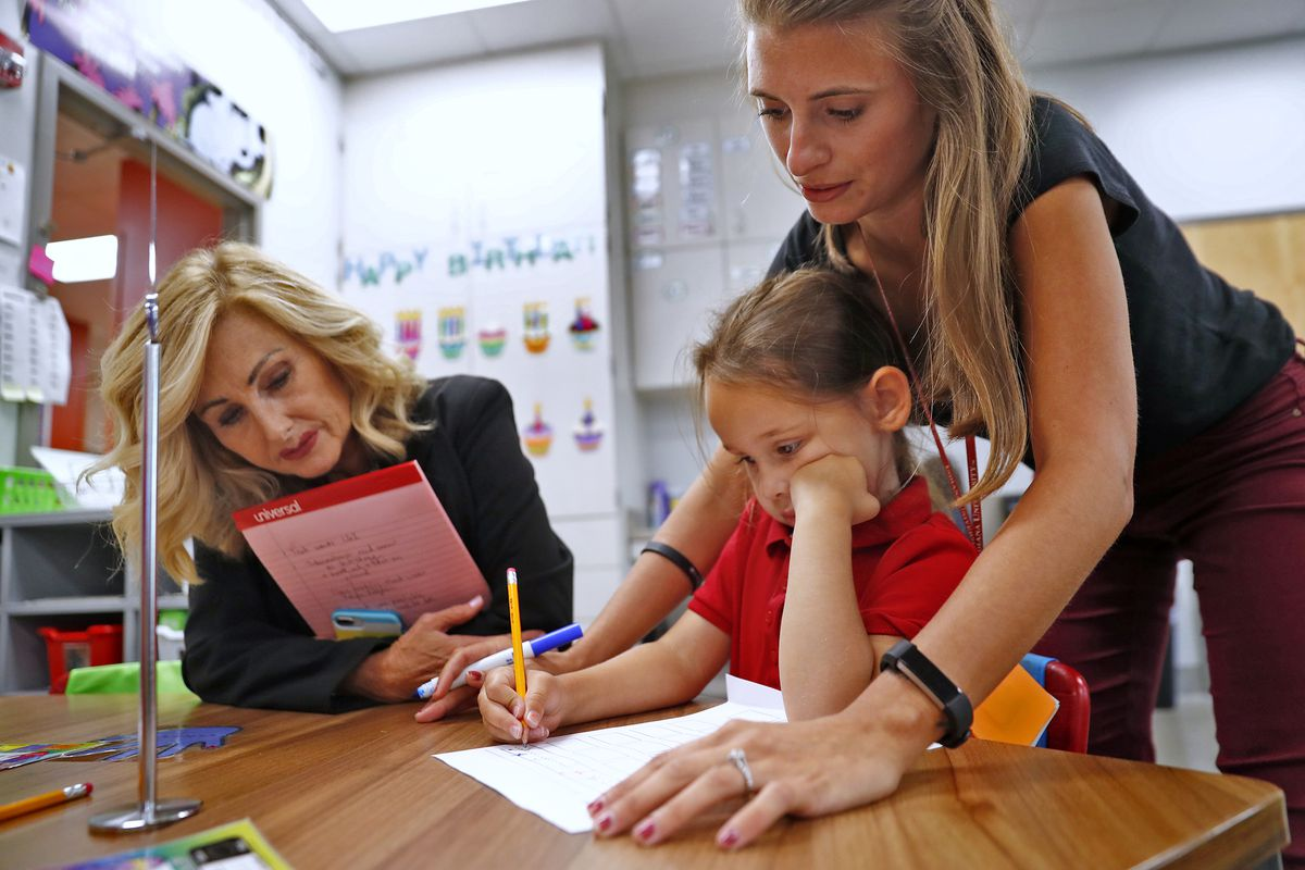 Vickie Carpenter, Assistant Superintendent of Elementary Schools in Perry Township Schools, left, helps Kindergarten teacher Brooke Gagliola, right, work with Maya Dennis on a class exercise, at Jeremiah Gray Kindergarten Academy, Friday, August 2, 2019.