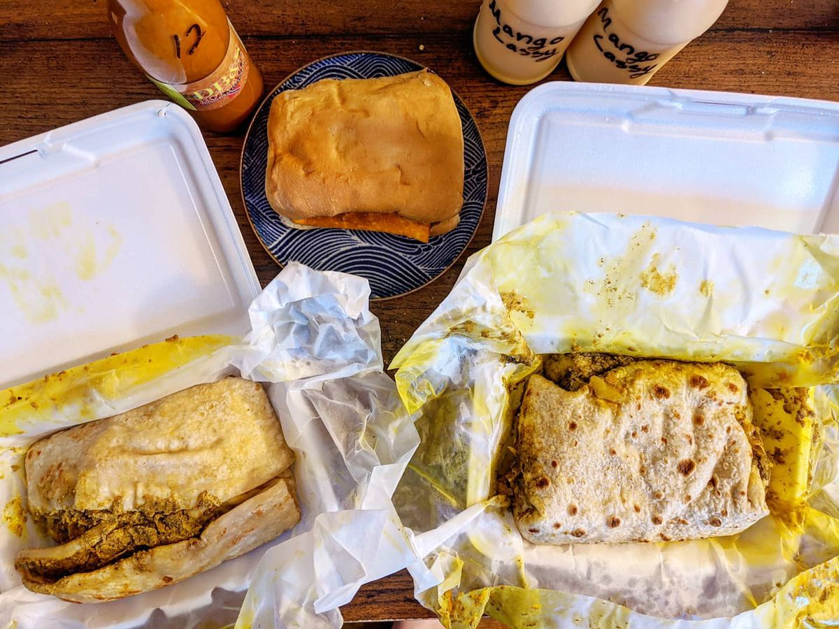 Overhead view of styrofoam takeout containers filled with two Trinidadian roti. There's also coco bread stuffed with a beef patty on a plate, two plastic bottles labeled mango lassi, and one glass bottle of an orange hot sauce.