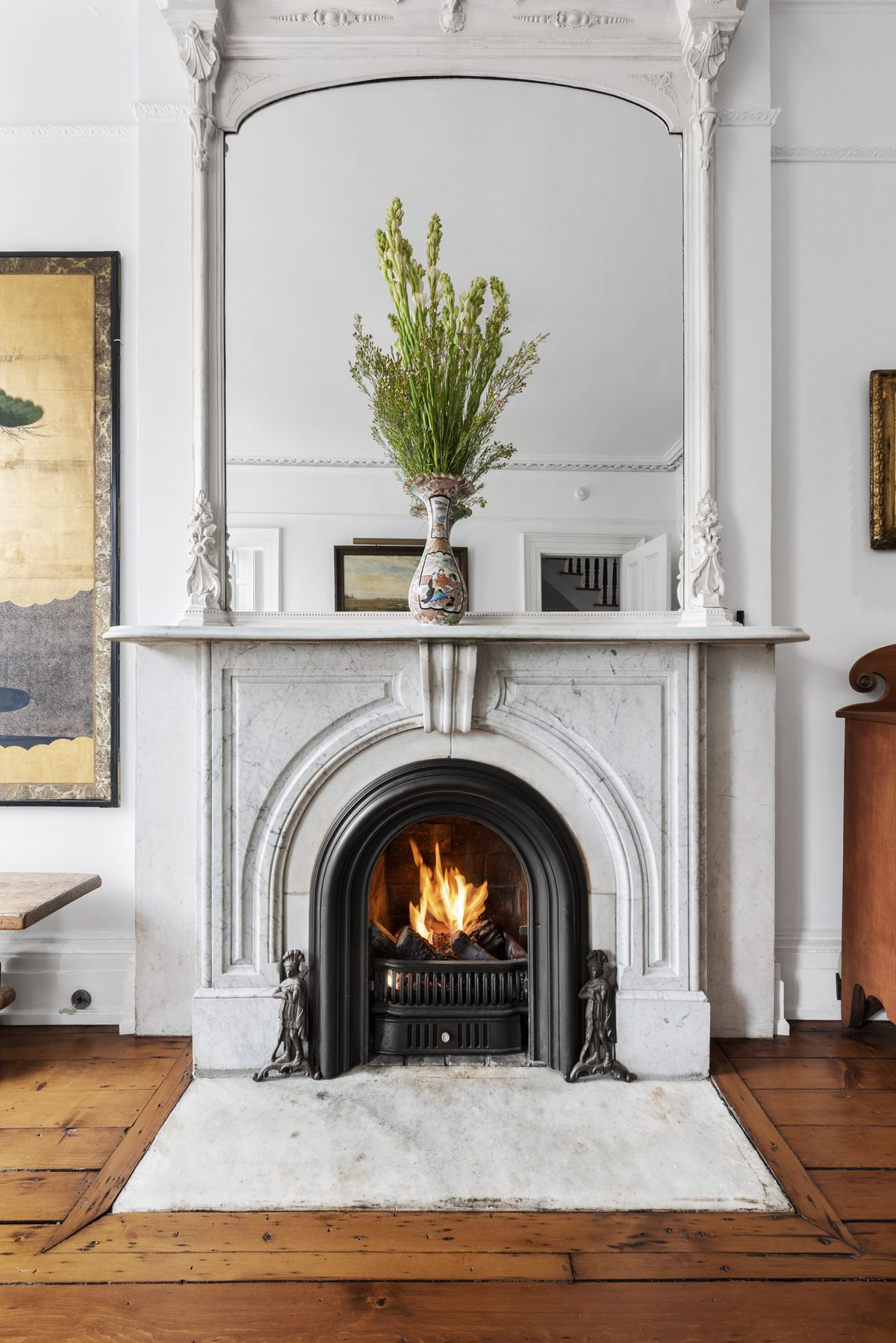 A wood-burning fireplace with a mantle.