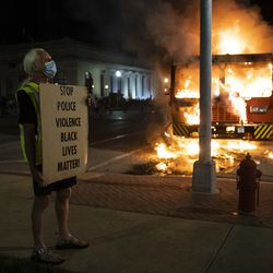 A protester stands near a burning truck outside the Kenosha County Courthouse, where police clashed with protesters in the second night of unrest after police shot Jacob Blake, Monday night, Aug. 24, 2020.