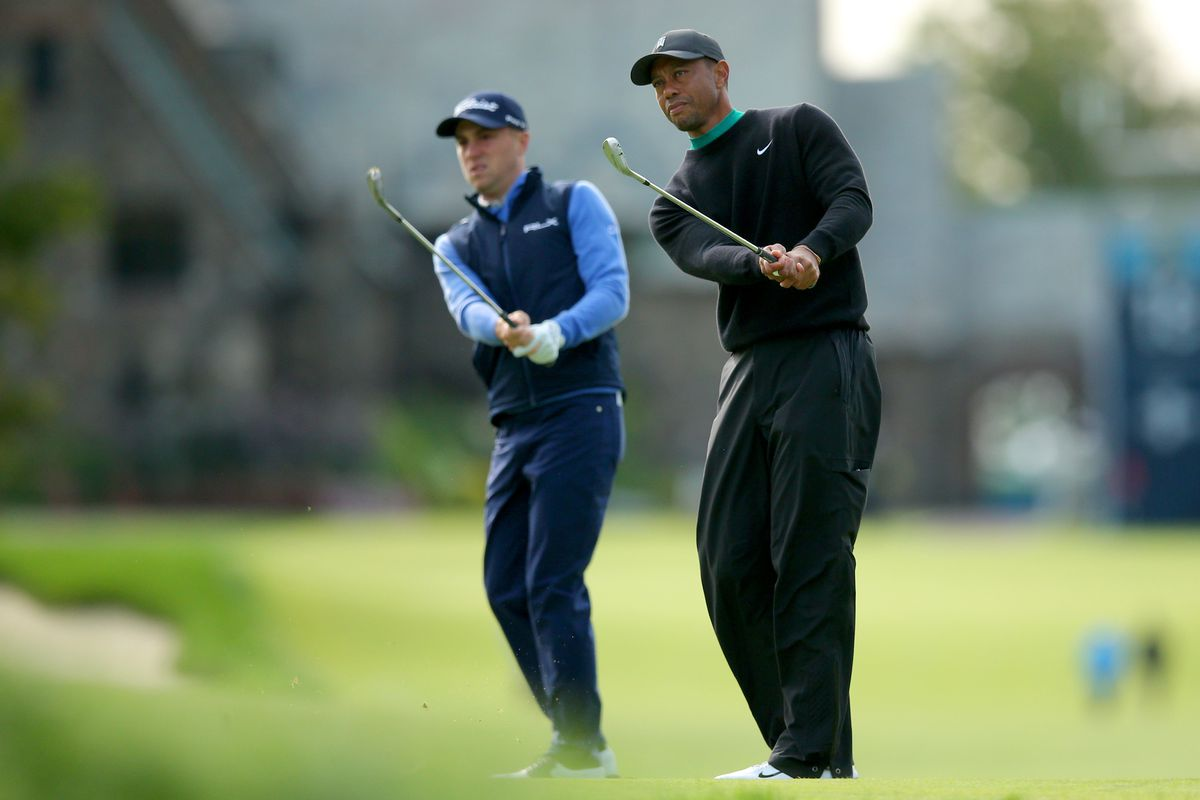 Tiger Woods and Justin Thomas chip from the eleventh fairway onto the green during a practice round for the 2020 U.S. Open golf tournament at Winged Foot Golf Club - West.