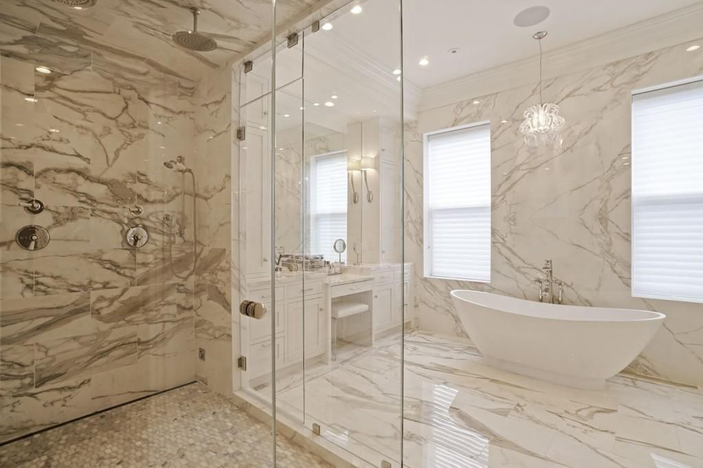 A marbled bathroom with a soaking tub and a shower with a glass door.