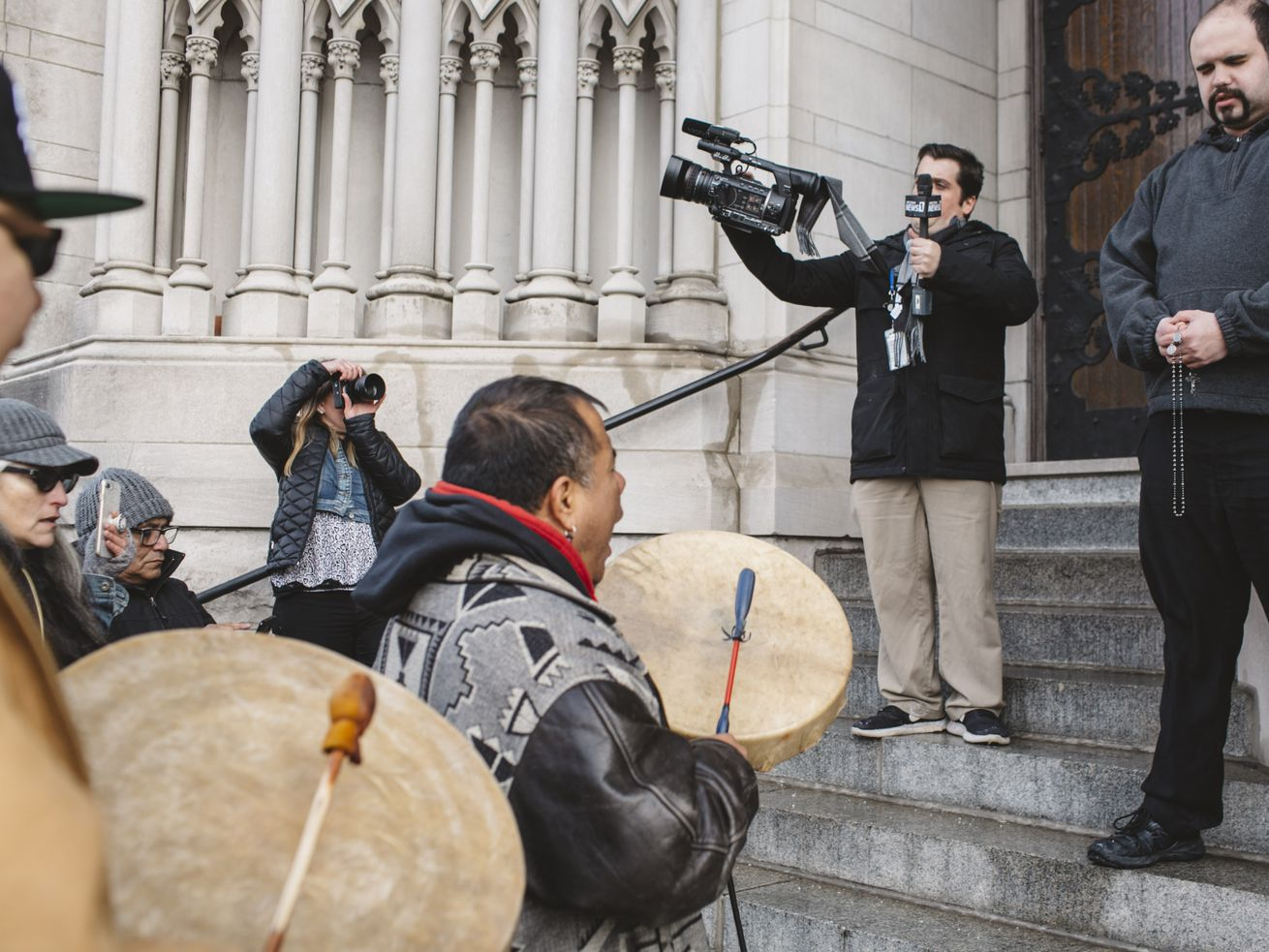 Sleepy Eye LaFromboise beats a drum as Nathaniel Hall, a diocese member, prays to a rosary, at a protest outside the Covington Catholic Diocese on January 22, 2019.