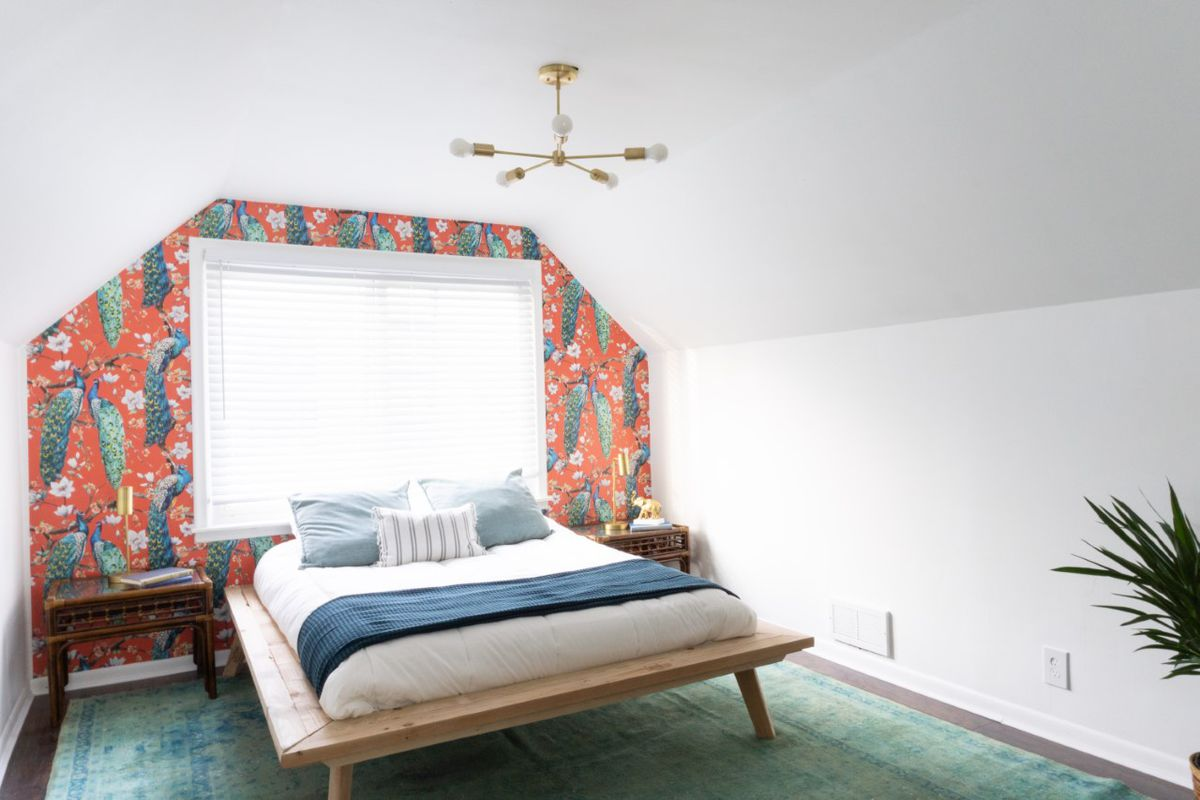 A large bed with a low-to-the-ground frame. There's white walls except for the one behind the bed which has peacocks against a red background.