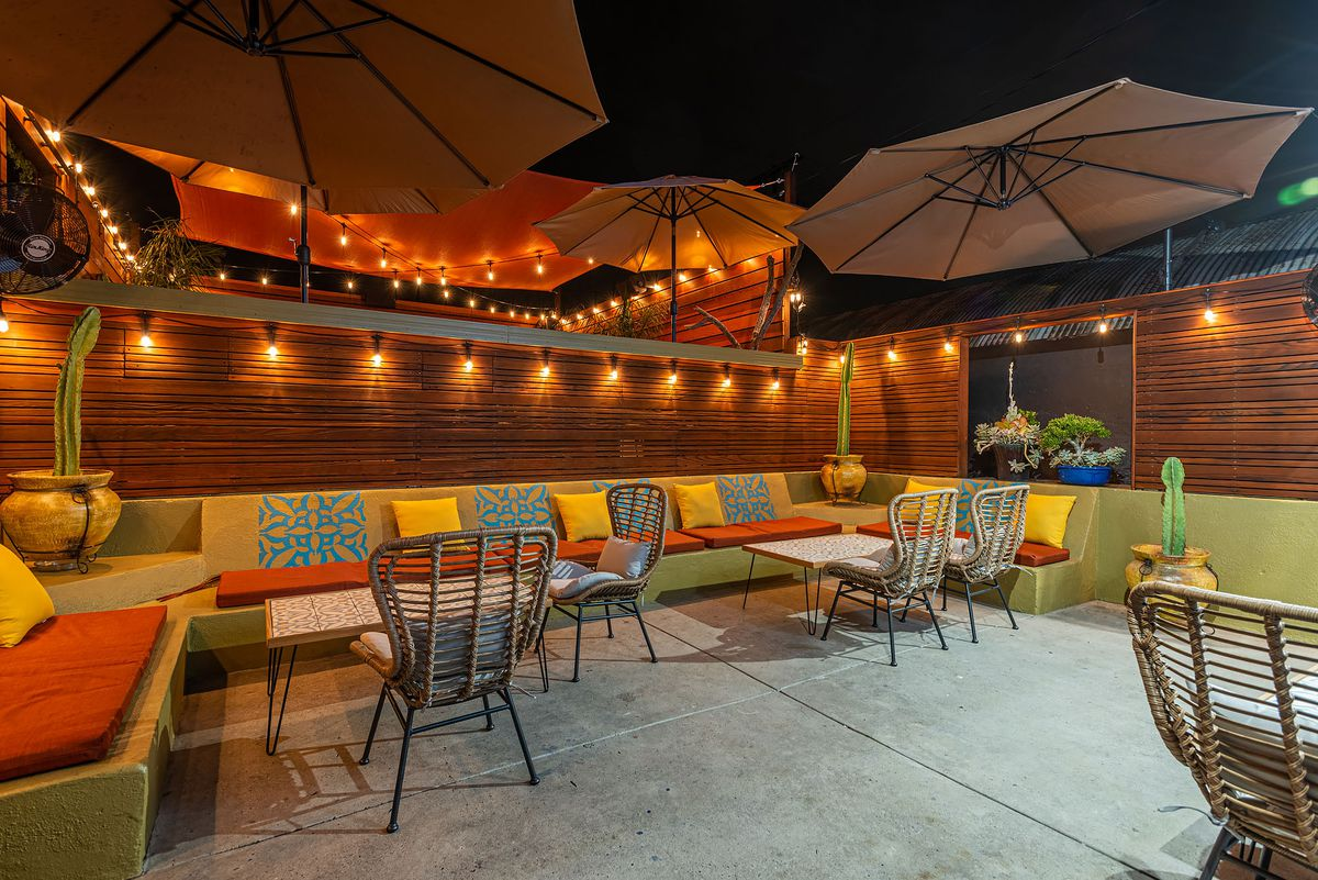 Colorful pillows show off Nativo's outdoor dining area at a new restaurant, at night in Los Angeles, California.
