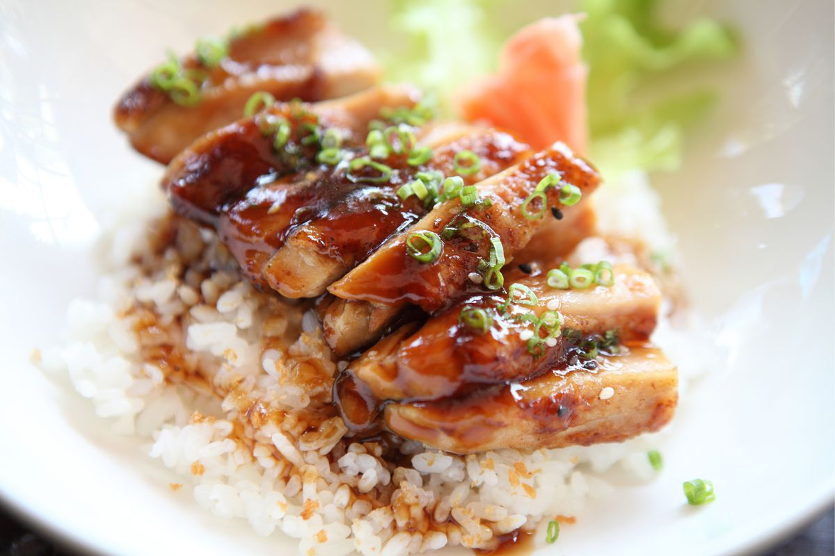 A plate of teriyaki chicken on top of white rice.
