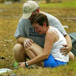 Frank Conaway comforts his wife, Pauline, as she gathers personal items from the yard of their home in Waveland, Miss., Thursday. Their home was destroyed.