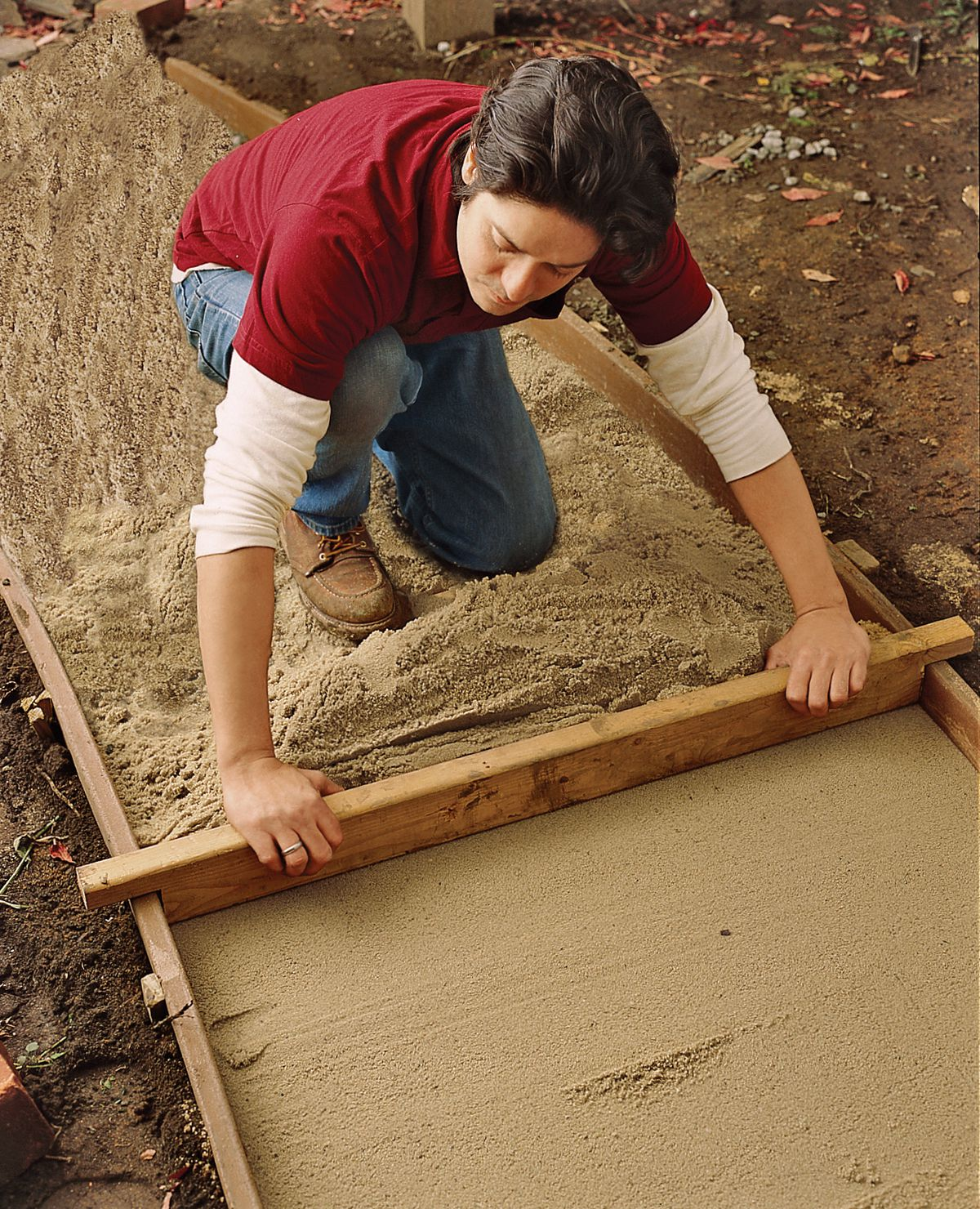 Man Adds Sand Layer To Brick Walkway