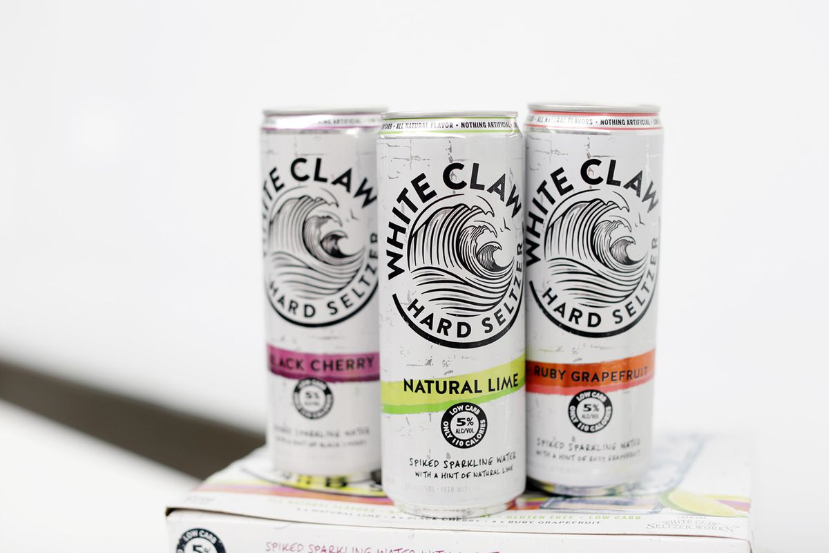 Three cans of White Claw sitting on a box against a white background.